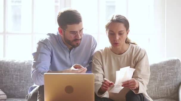 Couple small business owners entrepreneurs analyzing expenses sitting on couch