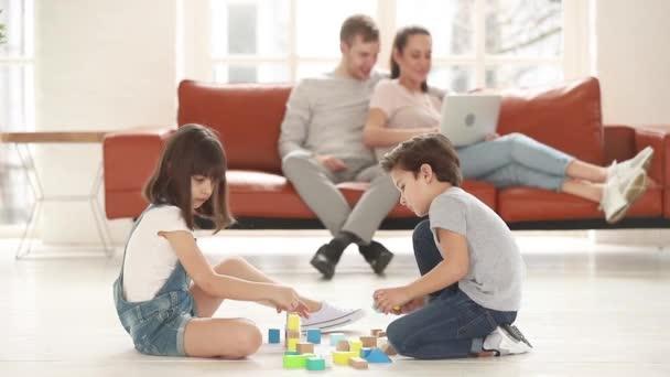 Děti si hrají s hračkou bloky nastavit sedí na teplé podlaze
