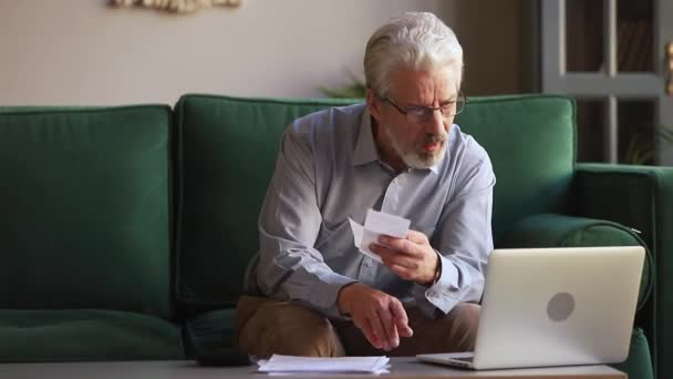 Elderly man manages personal budget using calculator calculates expenses