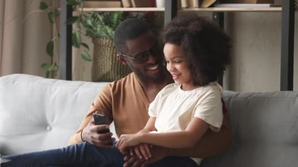 African father and daughter having fun using mobile music apps