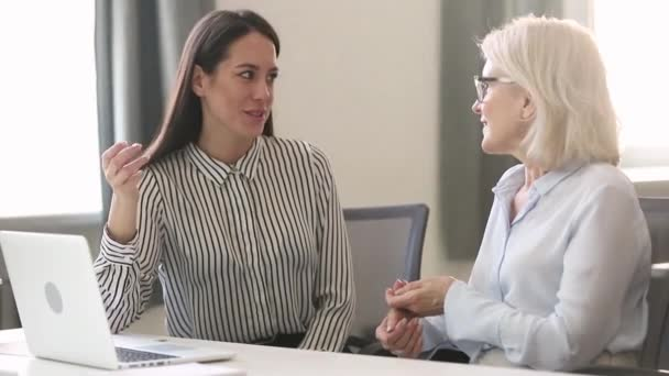 Different generations ages businesswomen sitting at desk discuss business issues