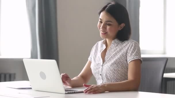Asian woman employee having informal conversation video call in workplace