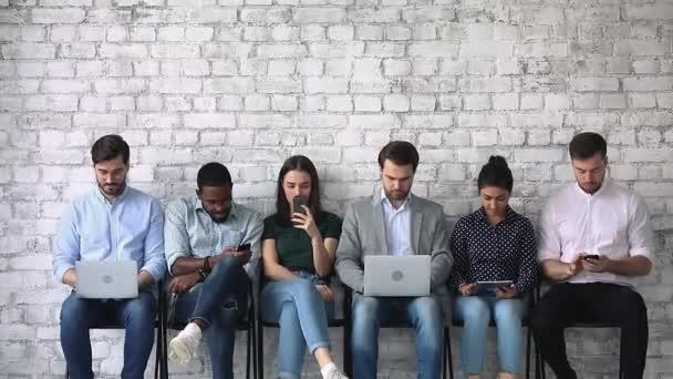 Různí mladí lidé s gadgets, čeká na pracovní pohovor.