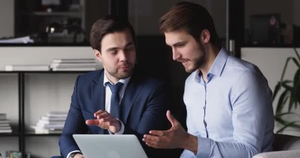 Két sikeres üzletember partner az online projektről tárgyal az irodában