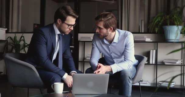 Két üzletember laptopot néz és irodai beszélgetéseket folytat.