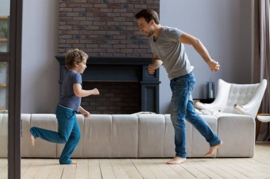 Young father have fun dancing with little son