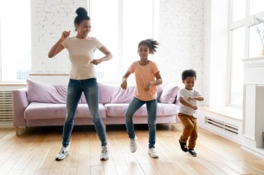 African mother teaches little children to dance in living room