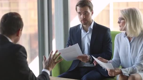 Businesspeople sitting office room having serious conflict about contract details