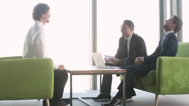 Tři pozitivní obchodníci se shromáždili v moderní kancelářské hale
