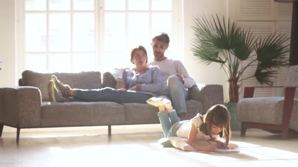 Zatímco dcera kreslí na teplou podlahu rodiče odpočívají na gauči