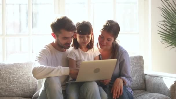 Happy family with daughter spending time at home using laptop