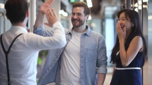 Happy diverse colleagues greeting talking standing in office hall