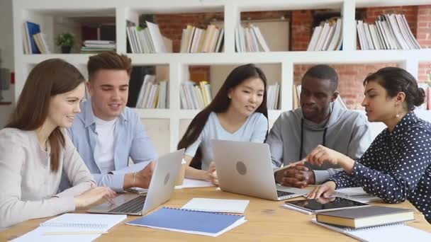 Focused diverse university students study using laptops prepare for exam
