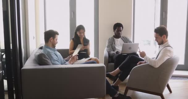 Diverse business people group sitting in office holding using devices