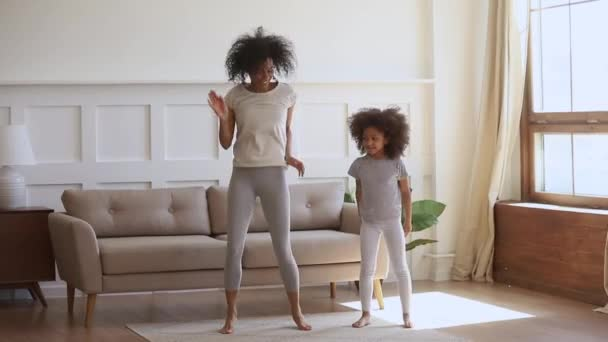 Active african mom and kid daughter jumping dancing at home