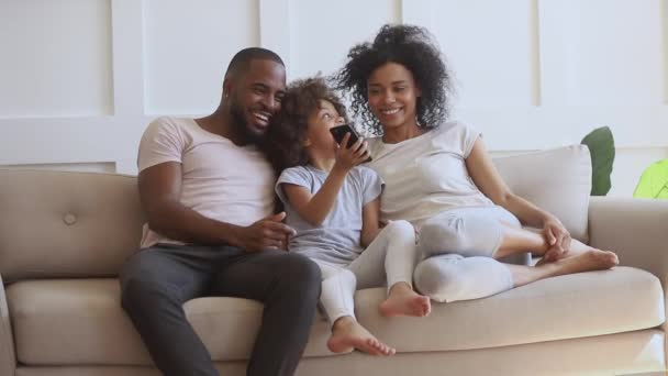 Happy african parents with kid daughter using smartphone on sofa