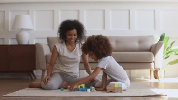 Happy little african kid daughter and mother playing on floor