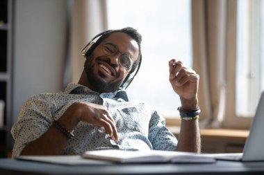 African man wear headphones listening song enjoy break at workplace