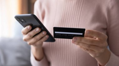 Close up woman paying online by credit card, using smartphone