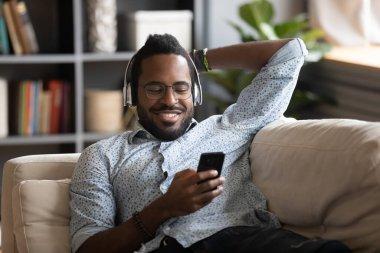 African guy holding cellphone listens music through wireless headphones