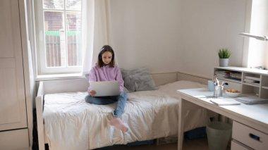 Teenage girl in headphones using laptop in bedroom