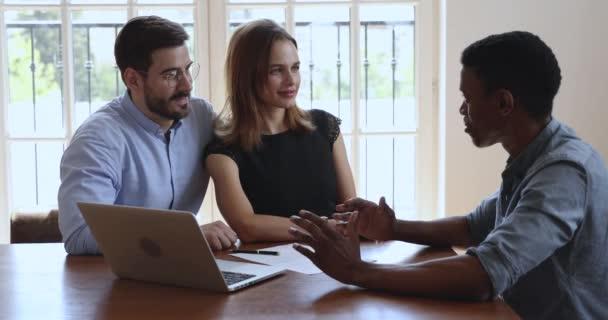 Glückliches kaukasisches Paar hört afrikanischem Manager zu, der über Hypothekengeschäft berät