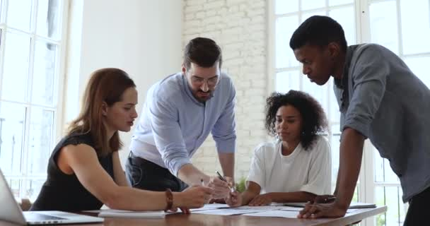 Fokussiertes multiethnisches Team analysiert Finanzbericht am Bürotisch