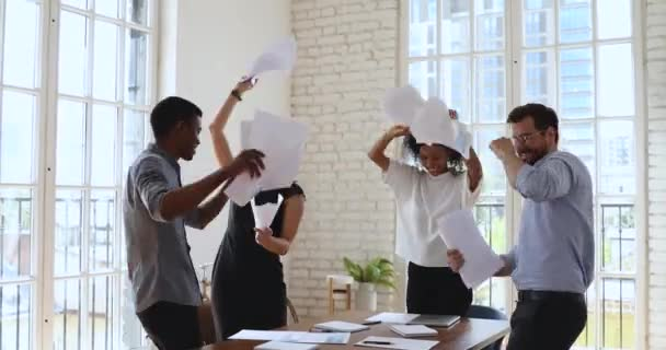Glückliches multiethnisches Business-Team, das im Büro mit Papieren um sich wirft