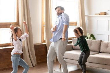 Happy father with son and daughter dancing in living room