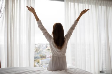 Back view of happy positive young female sit on bed stretch hands welcome new sunny day, overjoyed optimistic woman in white bathrobe wake up in bright bedroom meet good morning at home or hotel stock vector