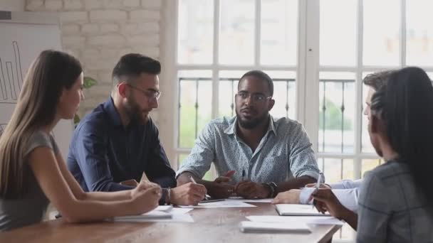 Serious black male boss explain strategy at multiracial group meeting