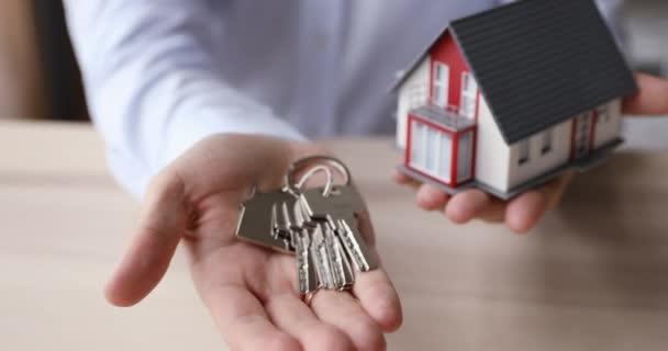 Realtor hand holding keys and tiny house layout closeup view