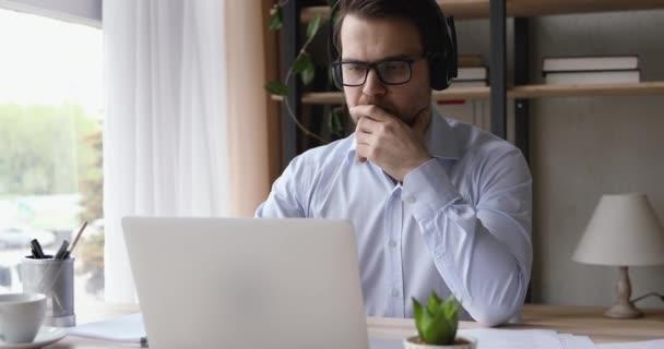 Serious man wears headset writing notes studying using laptop