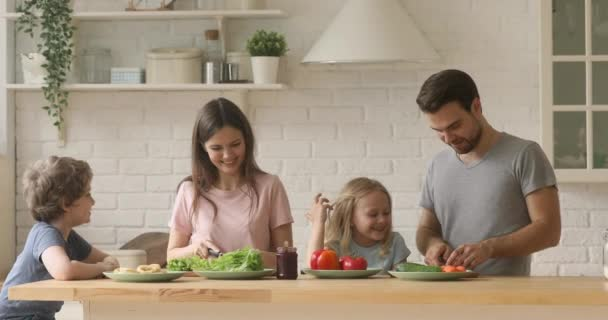 Happy parents and kids cutting salad cooking together in kitchen