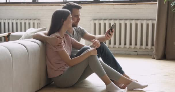 Happy young couple holding phone taking selfie sit on floor