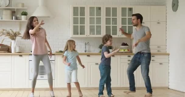 Lustige Eltern und süße Kinder haben Spaß beim Tanzen in der Küche