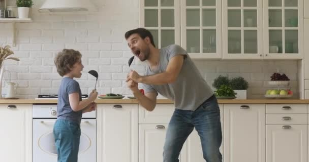 Funny artistic father and kid son singing song in kitchen