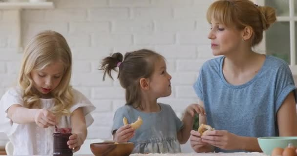 Cute kids daughters and happy mom eating cookies in kitchen