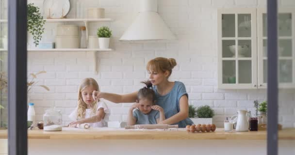 Happy mom and funny small daughters preparing dough in kitchen