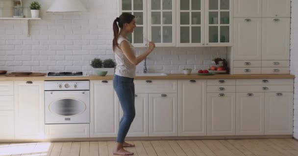 Funny happy girl dancing holding beater microphone singing in kitchen