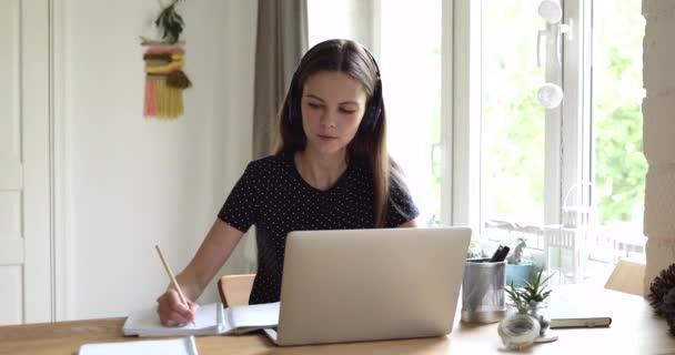 Diák lány írja a füzetbe, dolgozatot készít laptoppal