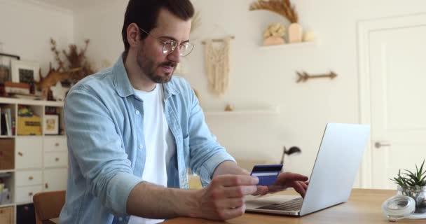 Mann tippt auf Laptop Kreditkartennummern ein, die er im Internet kauft