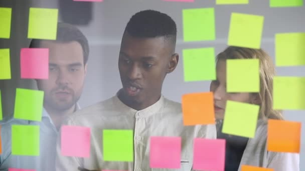Diverse team people brainstorm writing business ideas on sticky notes