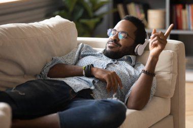 Satisfied positive African American man lying on couch, enjoying music