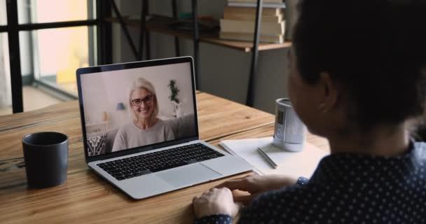 Rozhovor podle videokall notebook obrazovka pohled přes indické dívčí rameno