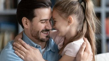 Close up smiling father and little daughter enjoying tender moment