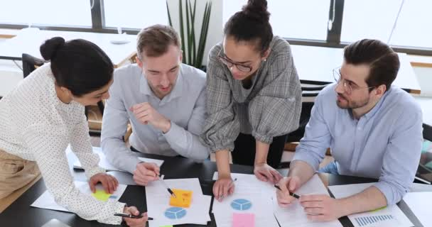 Multicultural employees group work together on project paperwork