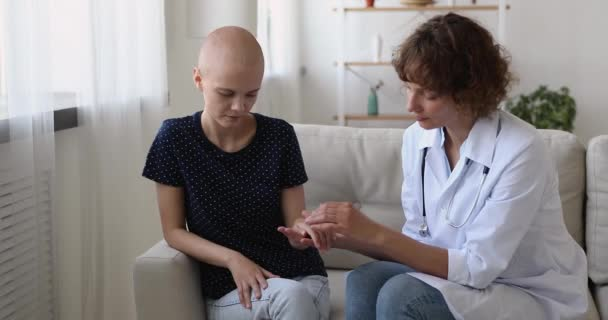 Female oncology nurse practitioner strokes hand of cancer patient