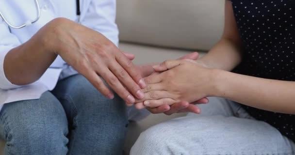 Nahaufnahme einer Ärztin, die Patientenhände hält und streichelt