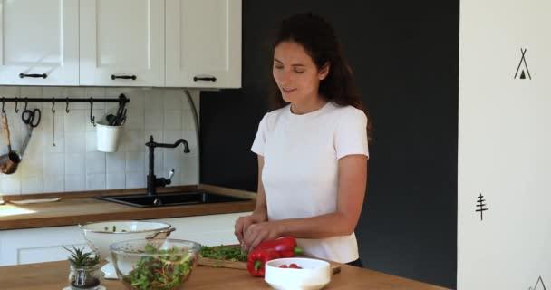 Frau steht in Küche und bereitet gesunden Vitamin-Sommersalat zu